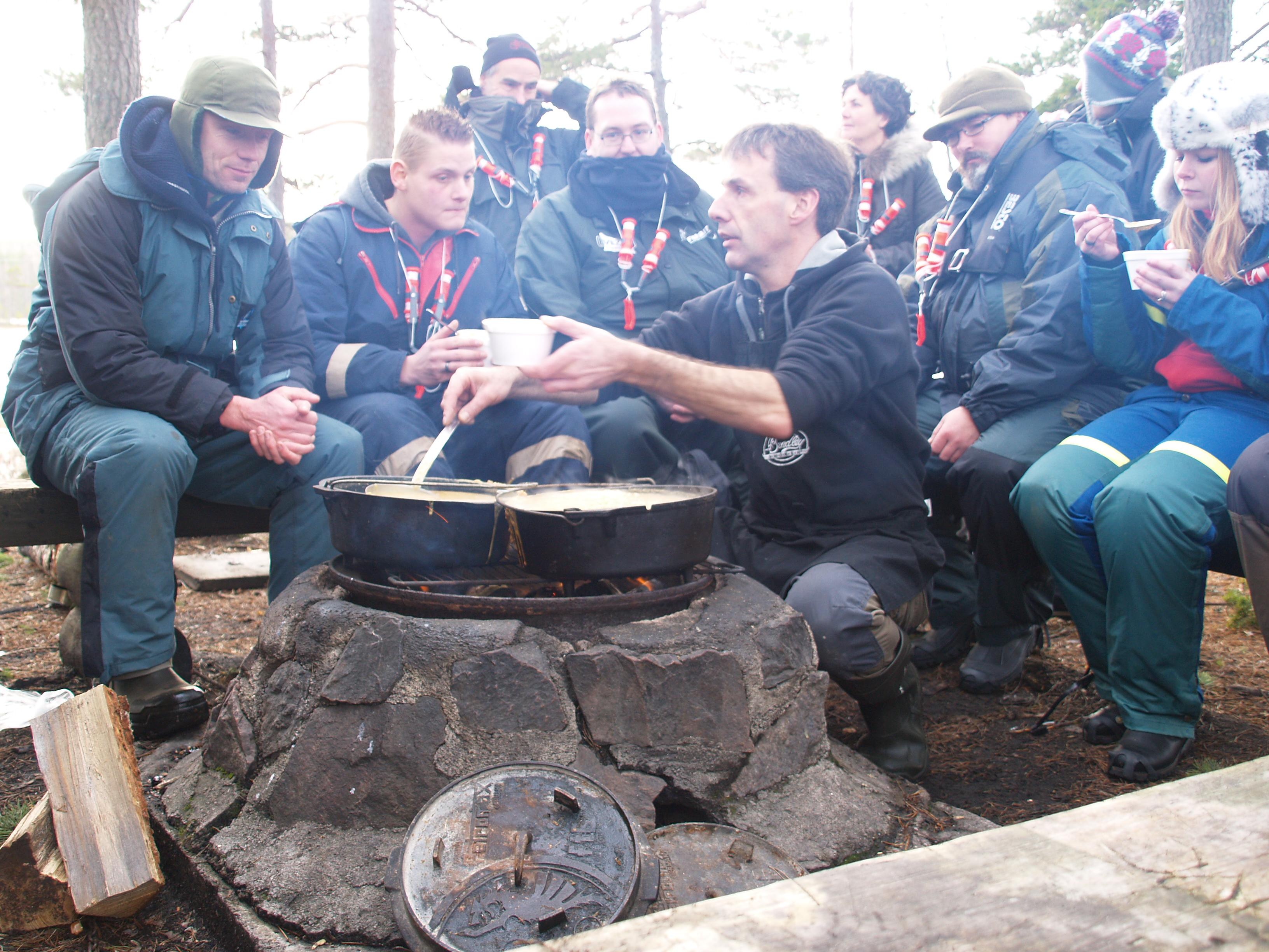 Johan Postma serviert am Lagerfeuer leckeres Essen, damit den Eisanglern wieder warm wird.